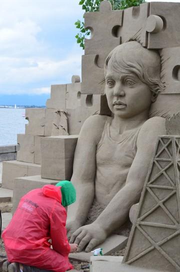 Mit Maurerkelle, Spachtel und Pinsel werden die Skulpturen aus gepressten Sandkuben herausmodelliert.